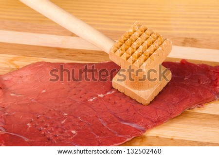 Hands tenderizing meat with a kitchen hammer