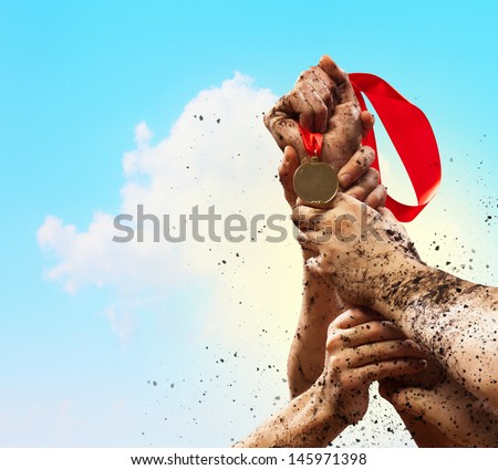 Hands tighten medal in a dark blue sky. - stock photo