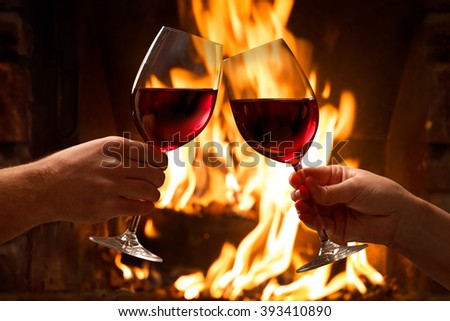 Hands toasting wine glasses in front of lit fireplace - stock photo