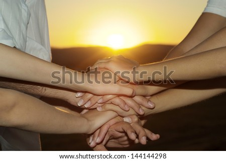 hands together against the sunset - stock photo