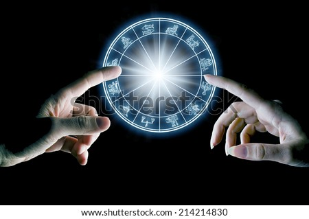 hands touching astrology wheel - stock photo