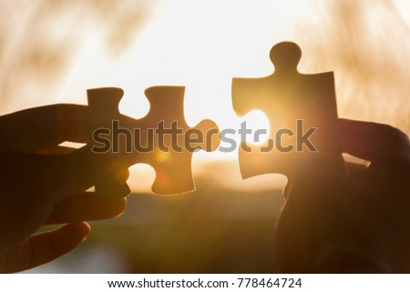 hands trying to connect puzzle piece To fill the missing pieces. jigsaw puzzle piece with light glow symbol of connection. business strategy concept. with light nature on background soft focus