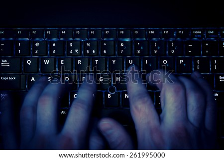 hands typing on keyboard in blue light with motion blur - stock photo
