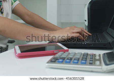 Hands typing on keyboard laptop with smart phone and calculator - stock photo