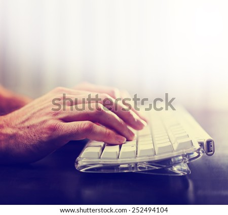 hands typing on laptop keyboard toned with a retro vintage instagram filter - stock photo