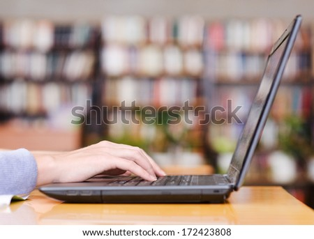 Hands typing on notebook in library - stock photo
