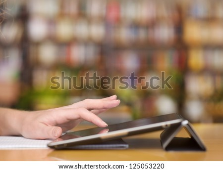 Hands typing on tablet computer in library