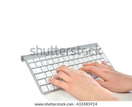 Hands typing on the remote wireless computer keyboard in an office at a workplace isolated on a white background