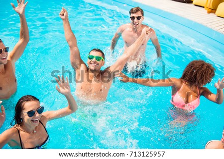 Hands up! Chilling international youth is doing aquaaerobics, enjoying on tourists resort, beach pool sunny disco in the water, in diverse trendy bikinies, spectacles, celebrating holiday dance motion