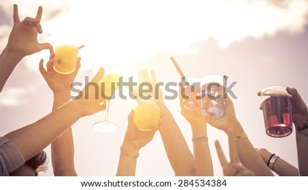 hands up to the sky with cocktails. people at music festival making party