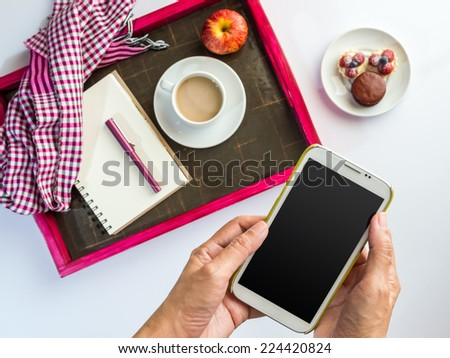 Hands using mobile phone with a wooden tray of light meal background - stock photo