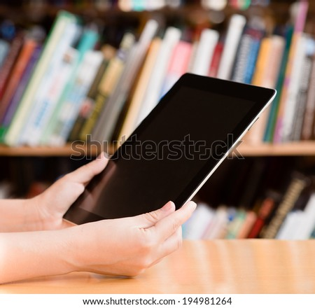 Hands using tablet computer in library - stock photo