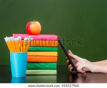 Hands using tablet computer near empty green chalkboard - stock photo