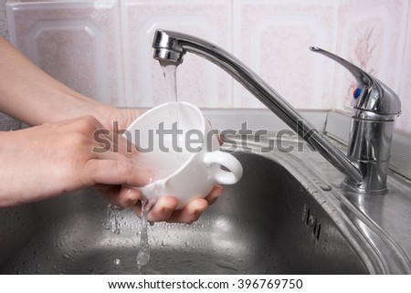 hands washing a cup