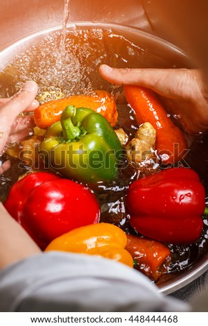Hands washing vegetables in water. Carrot and green paprika. Juicy vegetables for healthy snack. Appreciate the nature's gifts. - stock photo