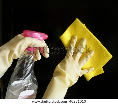 Hands wearing white rubber cleaning gloves holding a rag on one hand and spray bottle of detergent on the other. - stock photo