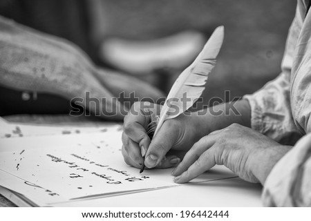 hands while writing a letter with a plume in black and white - stock photo