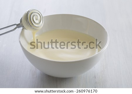 hands whisking egg with sugar and vanilla for fondant  - stock photo