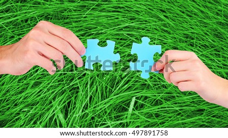 Hands with blue puzzle pieces on green grass background.