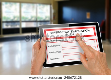 Hands with Computer Tablet completing Emergency Evacuation Plan App by Exit Doors - stock photo