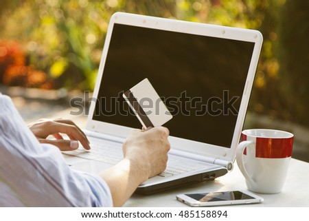 hands with credit card and laptop buying online