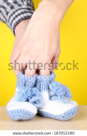 Hands with crocheted booties for baby, on color background - stock photo