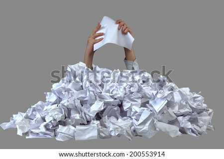 Hands with empty crushed paper reaches out from big heap of crumpled papers isolated on gray background - stock photo