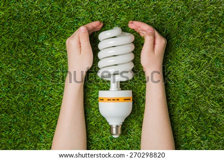 Hands with energy saving eco lamp over grass - stock photo