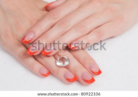 Hands with french manicure lying down and holding a gem