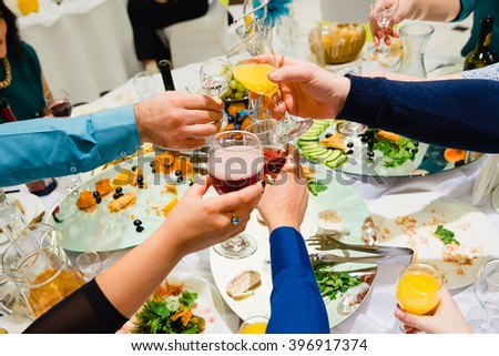 hands with glasses of wine clink and jingle - stock photo