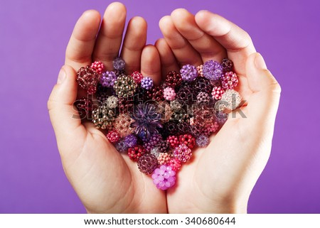 Hands with hand-woven beads in the shape of heart