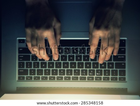 hands with laptop above typing in night - stock photo