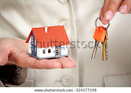 Hands with little house. Real estate and construction background. - stock photo