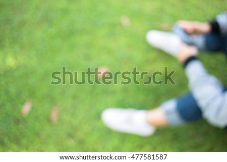 hands with long sleeve shirt holding mobile phone, sitting on green grass lawn, blurred