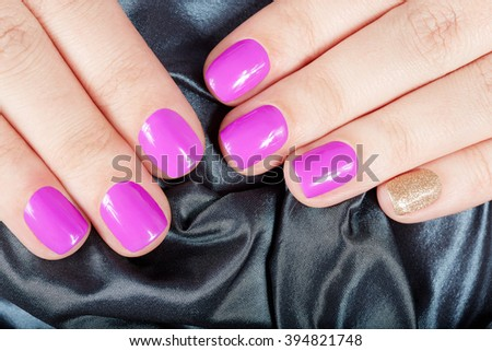 Hands with manicured nails covered with pink and gold nail polish on gray textile background - stock photo