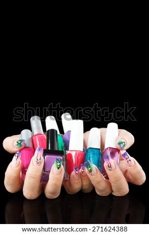Hands with manicured nails holding nail polish bottles on black background - stock photo