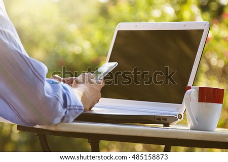 hands with mobile phone and laptop outdoors