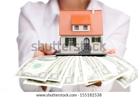 Hands with money and miniature house on a white background - stock photo