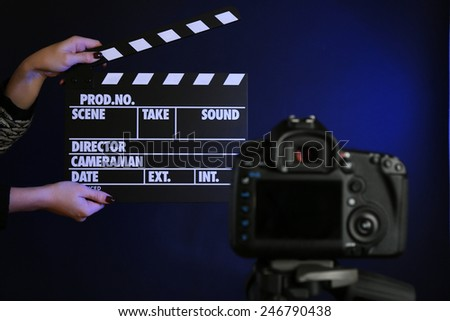 Hands with movie clapper board in front of camera on dark background - stock photo