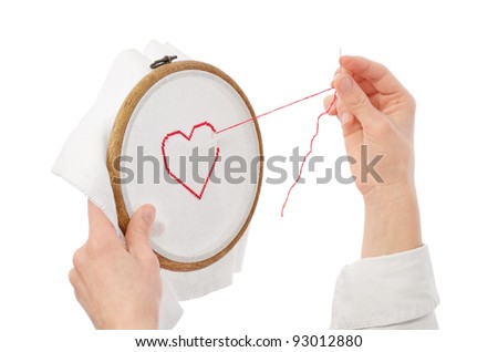 hands with needle embroidering red heart on white canvas - stock photo