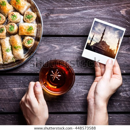 Hands with photo of Blue mosque in Istanbul and black tea near Turkish baklava on wooden background