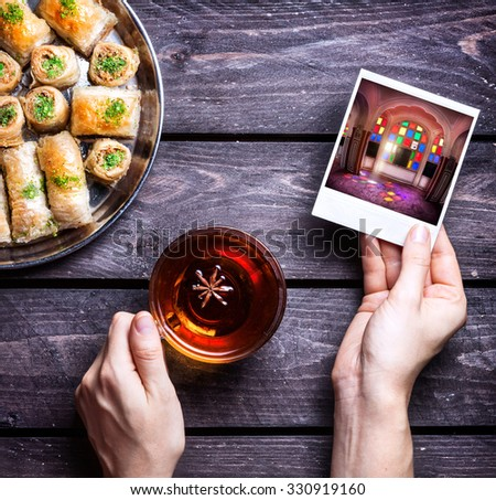 Hands with photo of Rajasthan palace and badyan tea near Turkish baklava on wooden background   - stock photo