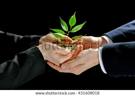 Hands with plant sprouting from a handful of coins on black  background