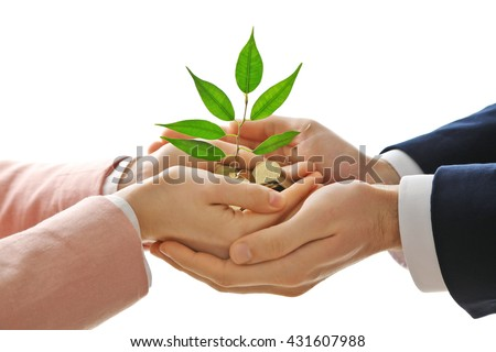 Hands with plant sprouting from a handful of coins on white background