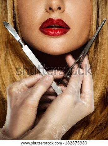 Hands with plastic surgery tools near young woman face  - stock photo
