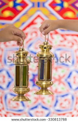 Hands with Ramadan Lantern over Ramadan Fabric - stock photo