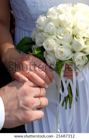 hands with rings and the wedding bouquet of flowers