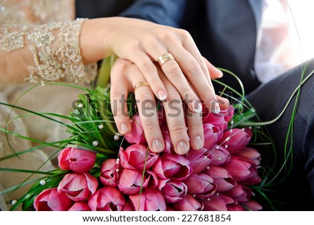Hands with rings bride and groom on the wedding bouquet of pink tulips. - stock photo