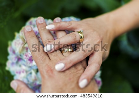 Hands with rings on flowers.