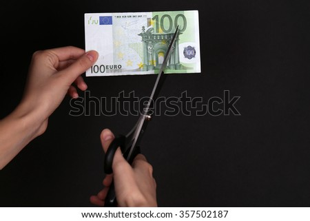 Hands with scissors cutting Euro banknote, on black background